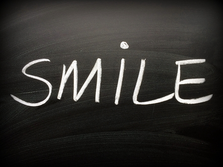 The word Smile written by hand in white chalk on a blackboard Stock Photo