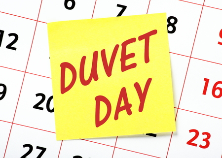 The words Duvet Day on a yellow sticky note with a calendar