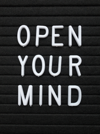 The words Open Your Mind in white plastic letters on a black letter board