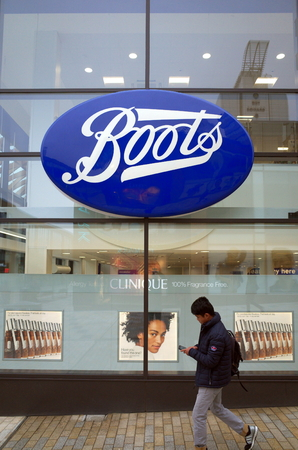Bracknell, England - April 16, 2018: A pedestrian passes by the window display of the Boots retail store and pharmacy in Bracknell, England.