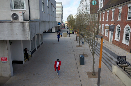 Bracknell, England - April 16, 2018: Wide angle view of old and modern buildings along the High Street with pedestrians, in the business and shopping district of Bracknell Town Centre, England