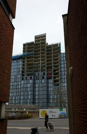Bracknell, England - December 10, 2018: Street level view between other buildings of a modern apartment block under construction, as a pedestrian passes by in Bracknell, England Editorial