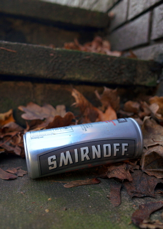 Bracknell, England - December 13, 2018: Discarded tin can of Smirnoff Vodka and Cola drink on concrete steps in an urban environment in England