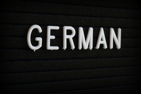 The word German in white plastic letters on a black notice board Stock Photo