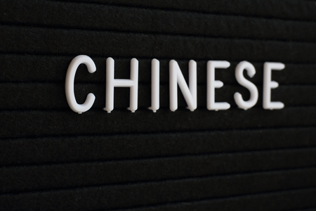 The word Chinese in white plastic letters on a black notice board