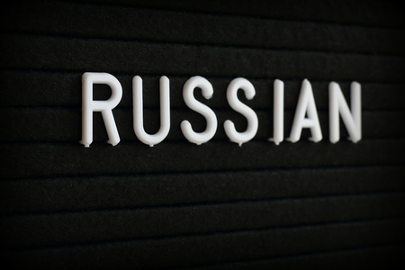 The word Russian in white plastic letters on a black notice board