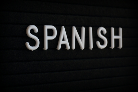 The word Spanish in white plastic letters on a black notice board