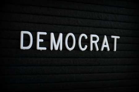 The word Democrat in white plastic letters on a black letter board