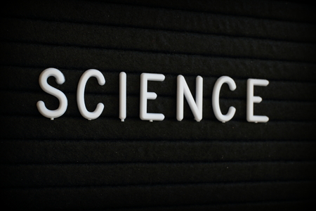 The word Science in white plastic letters on a black letter board