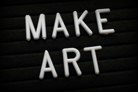 The phrase Make Art in white plastic letters pinned to a felt letter board