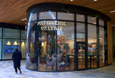 Bracknell, England - April 30, 2018: People inside and a pedestrian passing by the Patisserie Valerie store in Bracknell, England. A chain of cafes specializing in hand-made cakes, teas and coffees Editorial