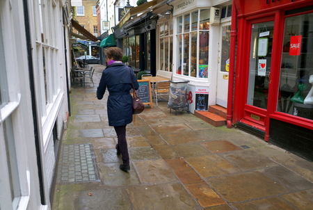 London,England - February 02, 2016: A pedestrian walks along one of the alleyways in the shopping district of the London Borough of Richmond in England