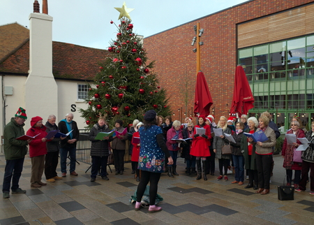 Bracknell,England - December 20, 2018: A large group of carol singers and their choirmaster perform in the front of the Christmas tree in Bracknell town centre in England