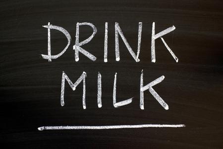 The words Drink Milk written by hand in white chalk on a blackboard