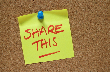 The words Share This written by hand on a yellow sticky note pinned to a cork notice board Stock Photo