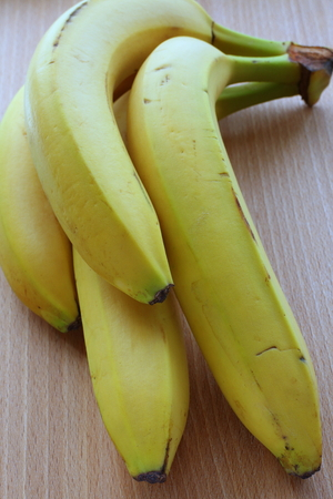 A bunch of almost ripe bananas on a wooden surface, photographed in natural light
