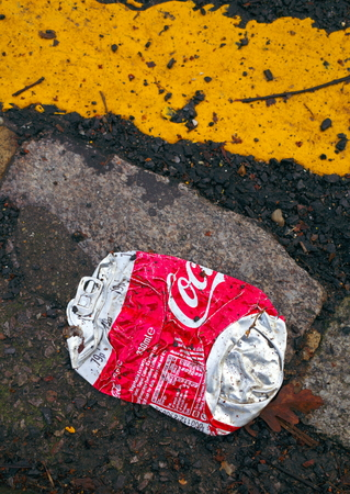 Bracknell, England - December 19, 2018: A flattened can of Coca Cola discarded by the yellow parking line on the side of a road in Bracknell, England