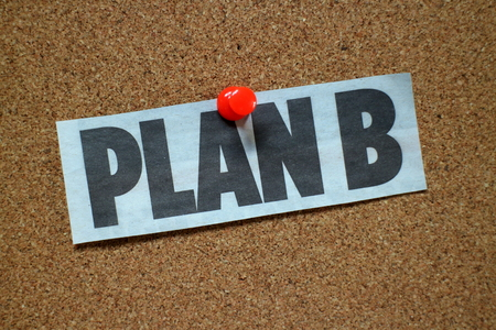 The words Plan B on a newspaper clipping cut out and pinned to a cork notice board