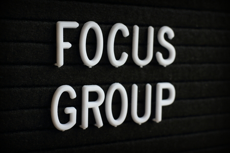 The words Focus Group in white plastic letters on a black felt notice board