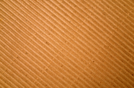 Brown corrugated cardboard paper background photographed on a diagonal