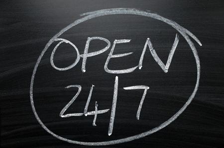 Open twenty four hours by seven written by hand in white chalk on a blackboard sign Stock Photo
