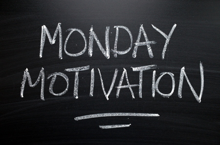 The words Monday Motivation written by hand in white chalk on a blackboard as a reminder Stock Photo