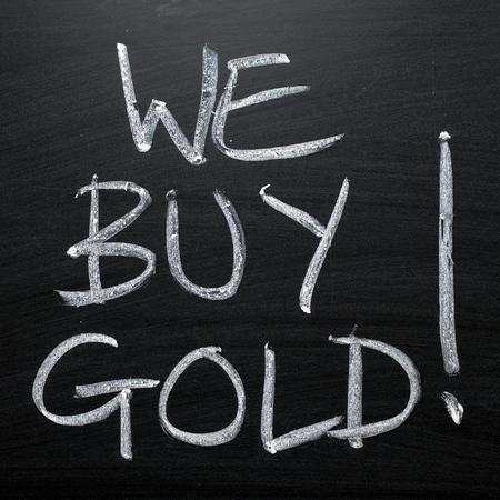 The phrase We Buy Gold written by hand in white chalk on a blackboard