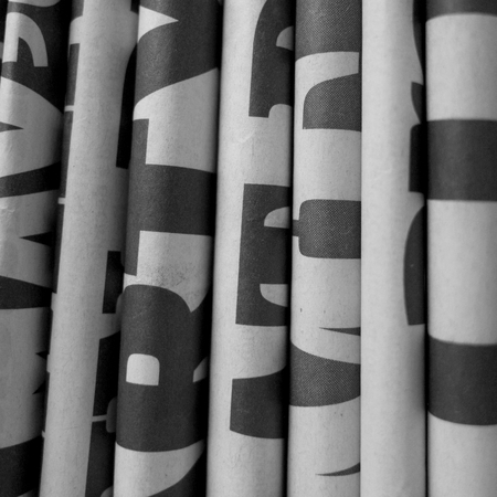 Black and white image of newspapers folded flat and in a vertical position