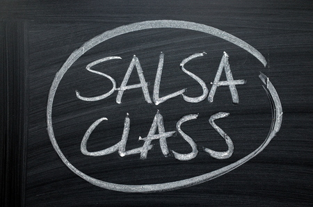The words Salsa Class written by hand in white chalk on a blackboard sign