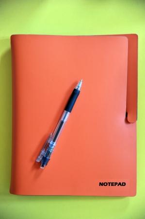 pen lying on a orange notebook Stock Photo - 16603684