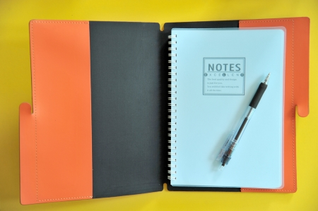 pen lying on a orange notebook Stock Photo - 16603686