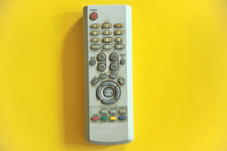 TV remote controls on yellow background  photo