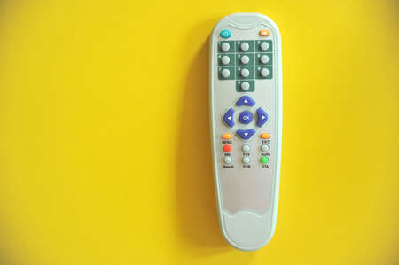 remote controls: TV remote controls on yellow background  Stock Photo