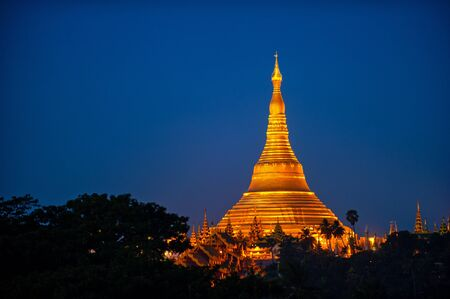 Shwedagon Pagoda Temple with village below in the twilight at Yangon, Myanmar  Burma  photo