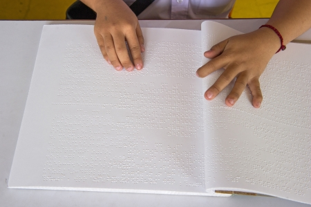 blind people: fingers and braille  blind people read a book in braille   Stock Photo