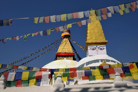 all seeing: Boudhanath Stupa. Golden spire and all seeing Buddha eyes on top a giant white hemisphere. Smaller stupa in foreground. Kathmandu, Nepal  Editorial