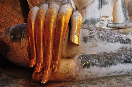 chums: gold leaf offerings on slender fingers of wat si chums iconic big buddha statue in sukhothai historic park northern thailand