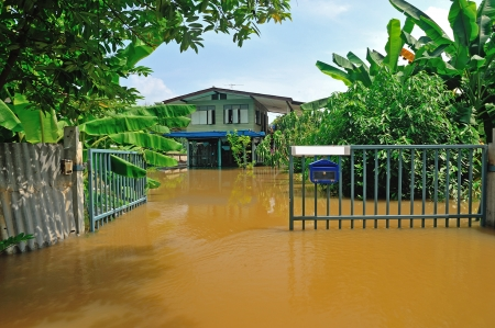 overtake: flood waters overtake a house in Thailand
