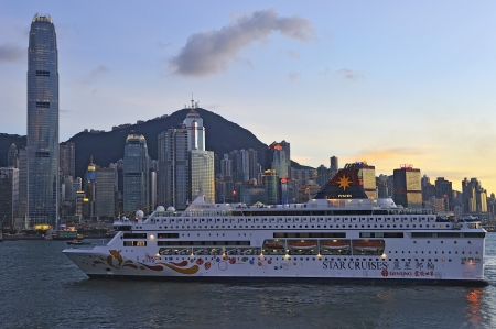 drove: HONG KONG - JULY 04: Victoria Harbor on July 4, 2012 in Hong Kong. Big Cruise Ship departed from Ocean Terminal and drove across Victoria Harbor at sunset.