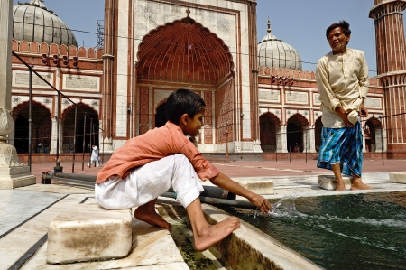 DELHI - AUG 08: A boy cleans himself in the courtyard of Jama Masjid Mosque on August 8, 2009 in Delhi, India.