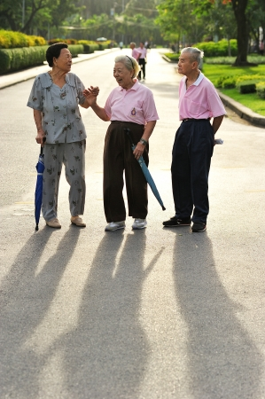BANGKOK THAILAND - Aug15- group of old people walking for excercise in Lumphini public park heart of Bangkok on Aug15, 2012 in Bangkok, Thailand  Editorial