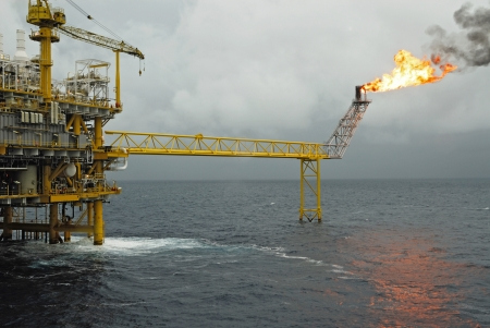 Oil and gas platform with gas burning in rain coming, Power energy.  photo