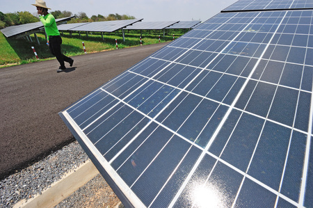 NAKORNRACHASRIMA, THAILAND - APRIL 21:  worker walking in solar farm  on April 21, 2011 in Nakornrachasrima, Thailand.