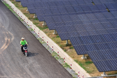 NAKORNRACHASRIMA, THAILAND - APRIL 21:  worker on bike in solar farm  on April 21, 2011 in Nakornrachasrima, Thailand.