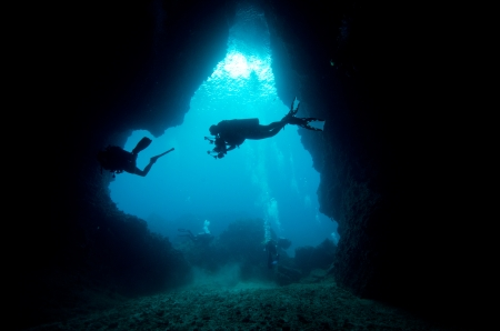 Scuba diver exploring an underwater cave framed in beams of sunlight, Similan, Thailand.  Stock Photo