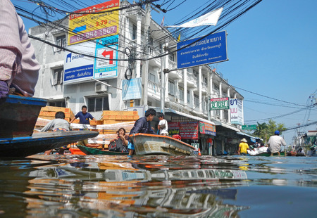 BANGKOK - NOVEMBER 11: A group of people evacuates from the flooded area at Taling Chan district during the massive flood crisis on November 11, 2011 in Bangkok.