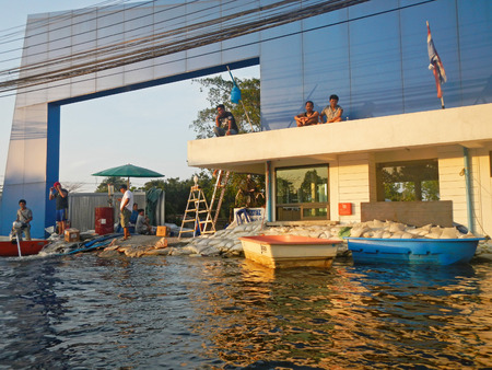 BANGKOK - NOVEMBER 16: A group of people evacuates from the flooded area at Taling Chan district during the massive flood crisis on November 16, 2011 in Bangkok.