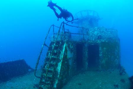 divers exploring the ship wreck in tropical sea Stock Photo