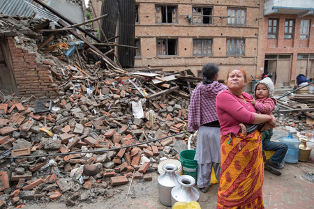 KATHMANDU, NEPAL - APRIL 30, 2015: Nepalese women wait to fill buckets with water at Pakhtapur in Kathmandu.