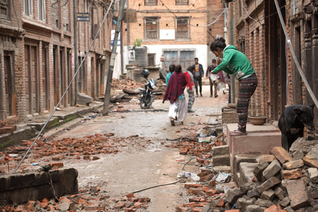 richter: KATHMANDU, NEPAL - APRIL 30, 2015: People are seen among the debris of buildings in the Bhaktapur city, 20km from the capital Kathmandu
